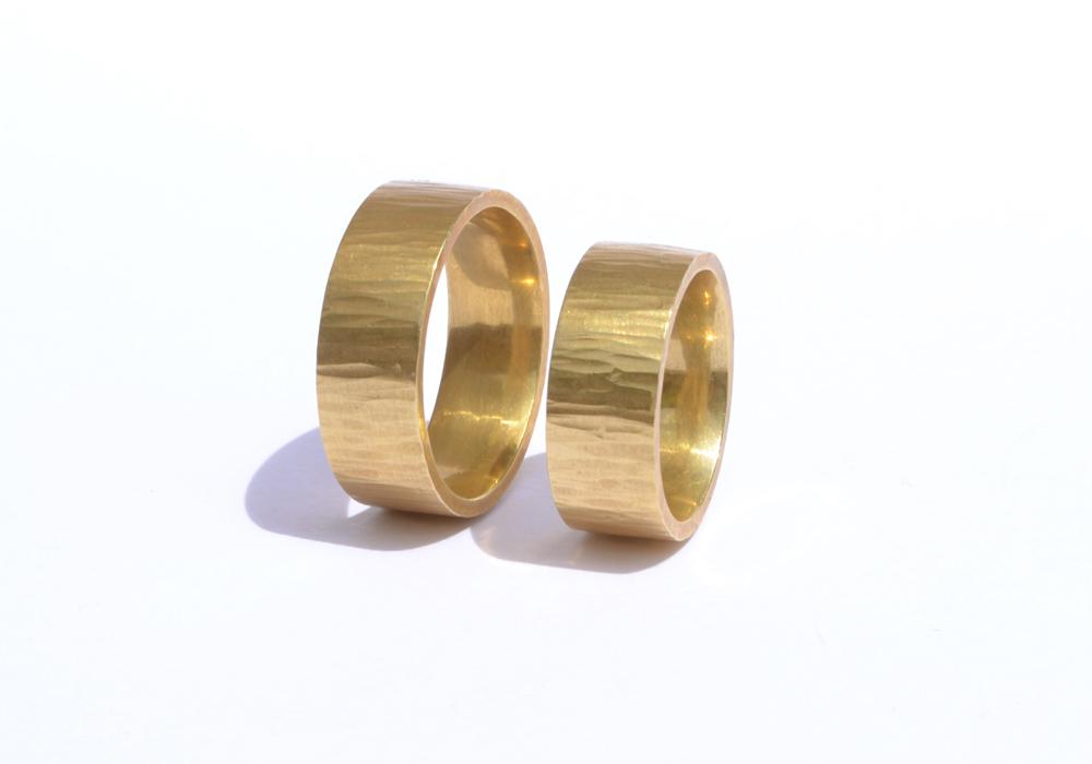 Trauringe aus 750er-Gelbgold, Profil: flach vierkant, Oberfläche: mit Finne geschmiedet